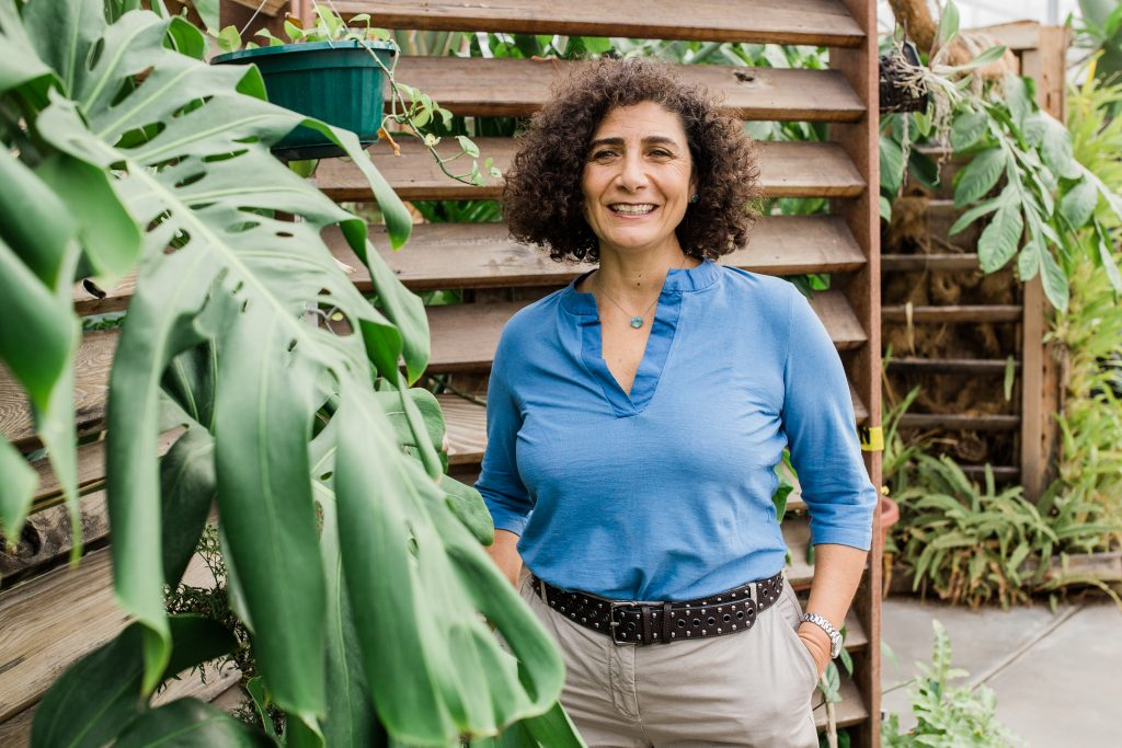 A woman with curly hair wearing a blue shirt and posing near green foliage